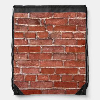 Bakstenen muur rugzakken