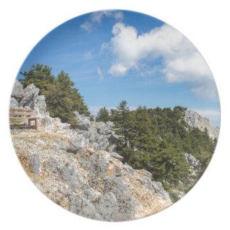 Bank op rotsachtige berg met bomen en blauwe hemel bord