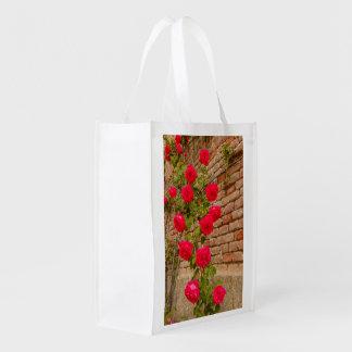 beklimmen de rozen op een bakstenen muur op boodschappentas