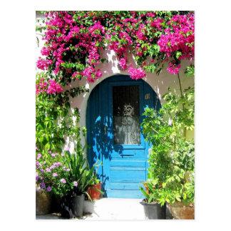 Blauwe die deur met mooie bougainvillea wordt briefkaart