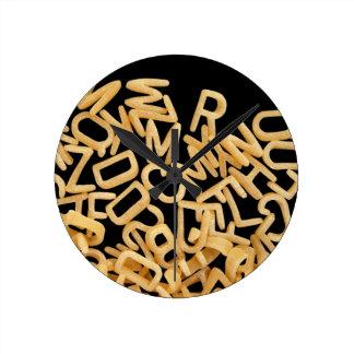 de achtergrond van alfabetdeegwaren ronde klok