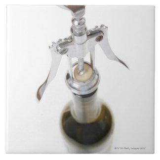 De fles van de wijn met kurketrekker tegeltje
