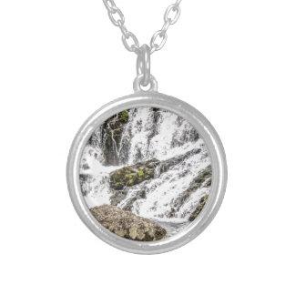 de kreken giet over rotsen zilver vergulden ketting