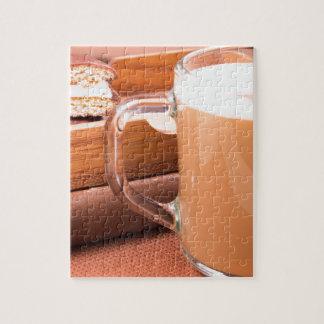 De mok van het glas met hete chocolade en koekjes puzzel
