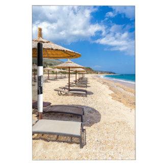 De paraplu's van het strand in rijen op zandig whiteboard