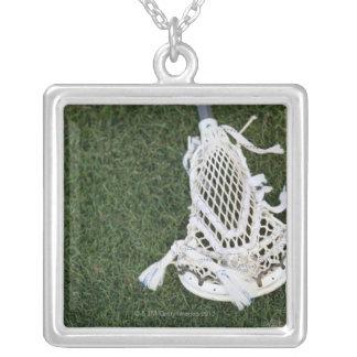 De stok van de lacrosse op gras zilver vergulden ketting