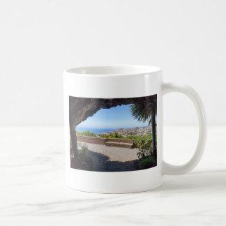 De vooruitzichten van het hol op zee en dorp op koffiemok
