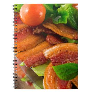 Detail van een bord van gebraden bacon en ringband notitieboek