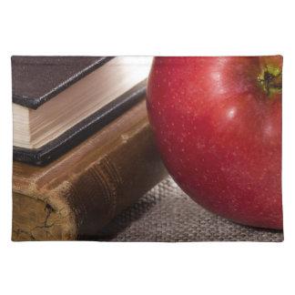 Detail van oude boeken in hardcover en rode appel placemat