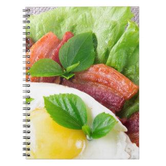 Dooier, gebraden bacon, kruiden en slaclose-up notitieboek