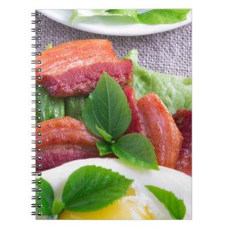 Dooier, gebraden bacon, kruiden en slaclose-up ringband notitieboek
