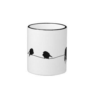 Drie kleine vogels die op een draad zitten mok gekleurder rand en oor