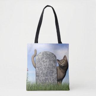 Droevige kat dichtbij grafsteen draagtas