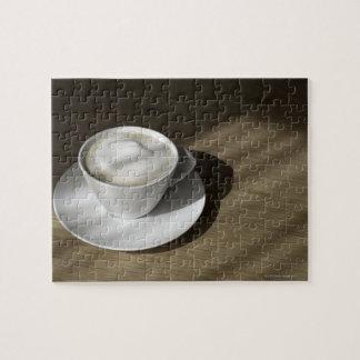 Een kop van cappuccino'skoffie ligt op een eik legpuzzel