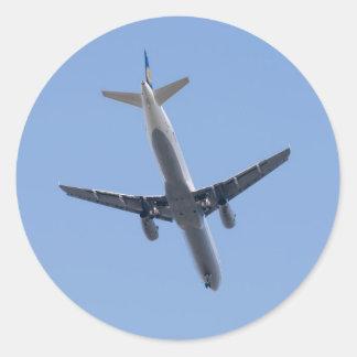 Enig vliegtuig op de blauwe hemelachtergrond ronde sticker