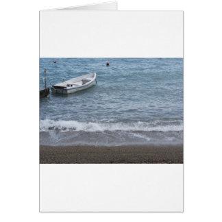 Enige het roeien boot die in een haven op het zee wenskaart