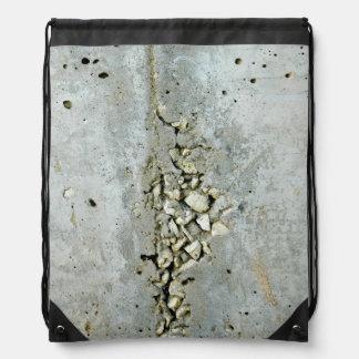 Gebarsten concrete muur met kleine stenen rugtassen
