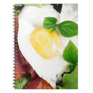 Gebraden eieren en bacon met kruiden en sla ringband notitieboek