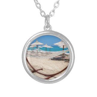 Hangmat met strandparaplu's bij kust zilver vergulden ketting