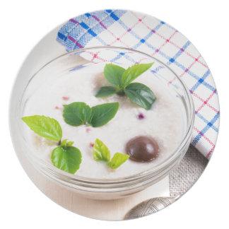 Havermeel in een kom glas met chocoladesnoep melamine+bord