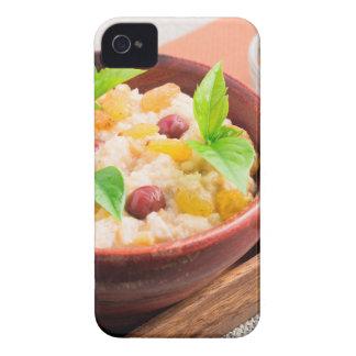 Havermeel met rozijnen en bessen in een houten kom iPhone 4 hoesje