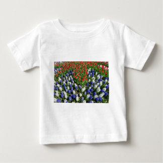 Het gebied van bloemen met rode blauwe tulpen en baby t shirts