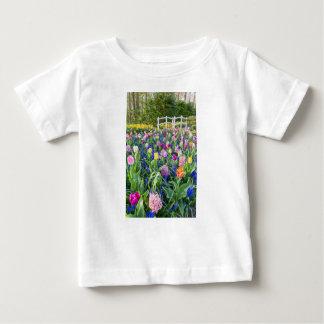 Het gebied van bloemen met tulpenhyacinten en brug baby t shirts