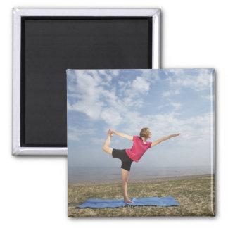 Het praktizeren van de vrouw yoga door het strand magneet