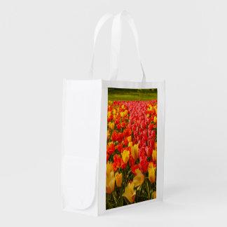 het tot bloei komen van tulpen op opnieuw te herbruikbare boodschappentas