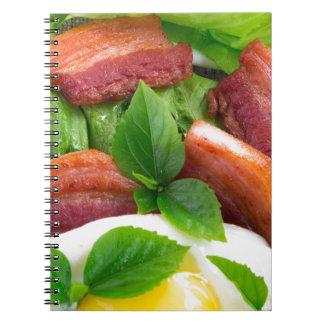 Hoogste uitzicht op eierdooier, gebraden bacon en ringband notitieboek