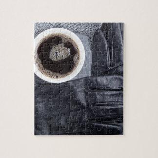Hoogste uitzicht van een witte kop koffie en puzzel