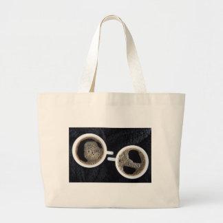 Hoogste uitzicht van twee kleine koppen van koffie grote draagtas