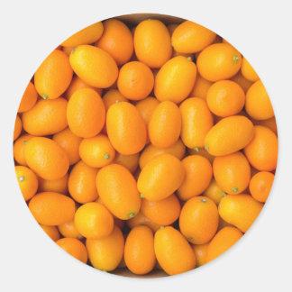 Hoop van oranje kumquats in kartondoos ronde sticker