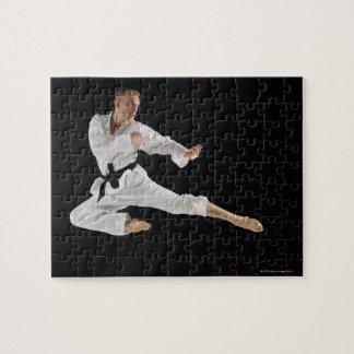 Jong man die karateschop op zwarte uitvoeren puzzel