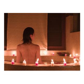 Jonge vrouw die bad met bloembloemblaadjes nemen briefkaart