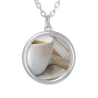 Kleine kop van espresso op een schotel met suiker zilver vergulden ketting