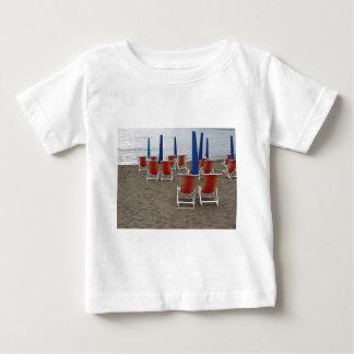 Kleurrijke houten stoelen bij zandstrand baby t shirts