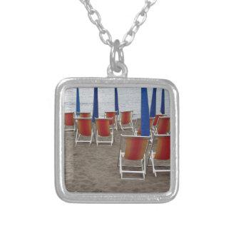 Kleurrijke houten stoelen bij zandstrand zilver vergulden ketting