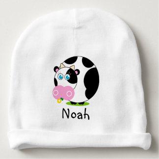 Leuke cartoon zwart-witte koe die een bloem eten, baby mutsje