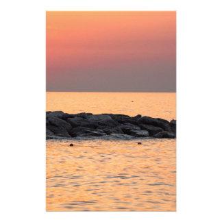 Man die bij zonsondergang vissen briefpapier