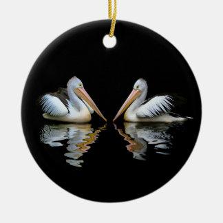 Mooie pelikanenbezinning over zwarte achtergrond rond keramisch ornament