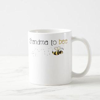 Oma aan de mok van de bijenkoffie
