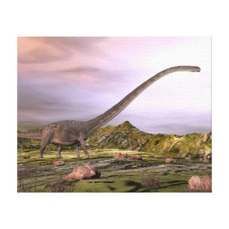 Omeisaurus die in de woestijn door zonsondergang canvas print