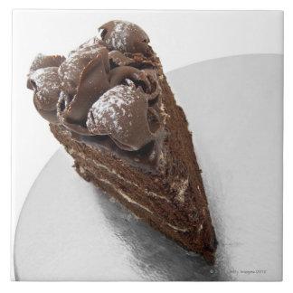 Opgeheven uitzicht van een stuk van chocoladecake tegeltje