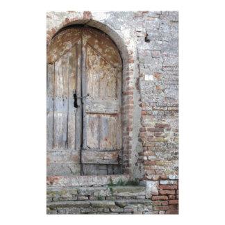 Oude houten deur in oude bakstenen muur briefpapier