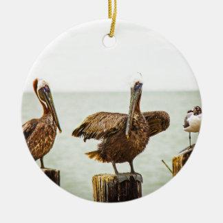 Pelikanen die op posten worden neergestreken rond keramisch ornament