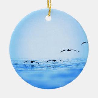 Pelikanen die over oceaan vliegen rond keramisch ornament