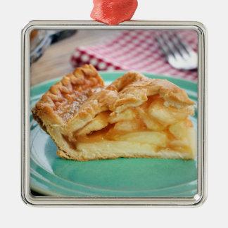 Plak van verse gebakken appeltaart op bord zilverkleurig vierkant ornament