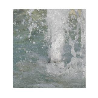 Plonsen van fonteinwater in een zonnige dag notitieblok