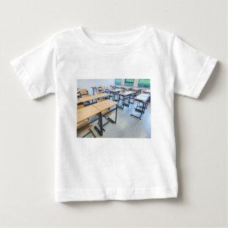 Rijen van lijsten en stoelen in klaslokaal baby t shirts